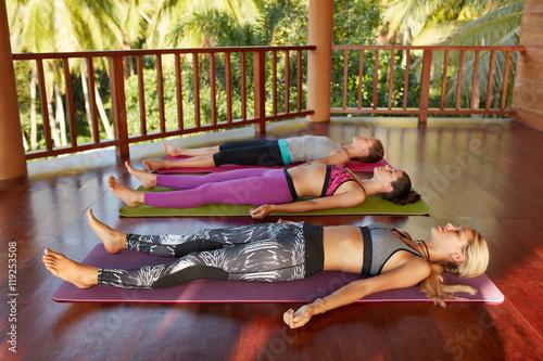 Poster Yoga class with women lying on floor , Savasana