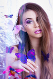 Gorgeous girl with creative makeup and purple butterflies
