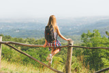Young female hiker with backpack sitting on the fence and enjoy the view.