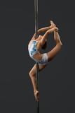 Modern dancer performing gymnastic split on pylon
