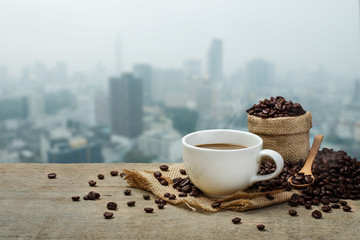 Hot Coffee cup with Coffee beans on the wooden table and the cit