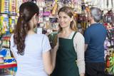 Saleswoman Looking At Customer Holding Dog Food Jar
