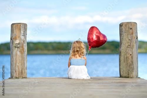 kleines Mädchen sitzt am See mit roten Herzluftballon Poster