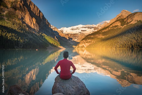 Poster Canada Man sit on rock watching Lake Louise reflections