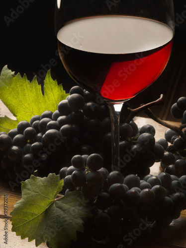 Fototapeta Glass with red wine and grapeson the wooden table