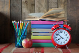 Alarm clock, pencils and a stack of books. Back to school.