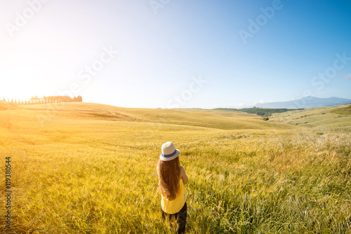 Spoed canvasdoek 2cm dik Meloen Young woman in hat and yellow shirt standing in the wheat field. Enjoying beautiful Tuscan landscape in Italy.