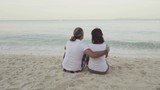 Man and woman sitting on the sand and looking at the sea. Full Hd stock footage clip