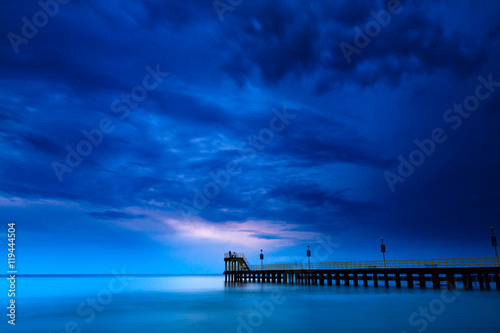 Sandy coast with dramatic sky and pier during sunset.