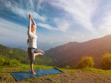 Woman in  yoga asana Vrikshasana tree pose in mountains outdoors