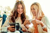 Fototapety Women using digital tablet in cafe