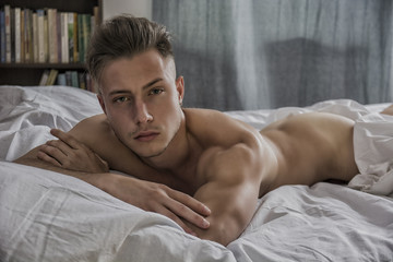 Totally naked sexy young man with muscular body on bed looking at camera