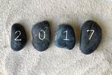 2017 inscrit sur galets noirs dans le sable