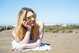 Girl lying on the sand at the beach with sunglasses heard shaped