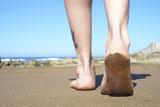 Female feet walking on beach closeup.