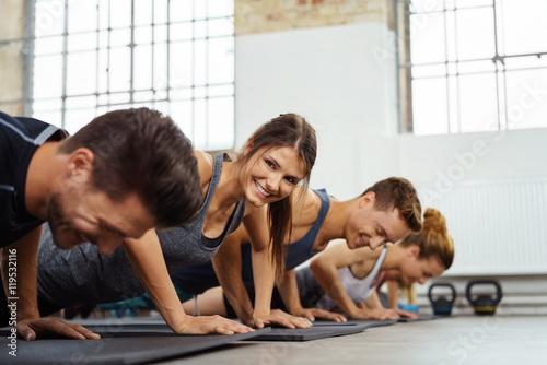 Poster lachende frau trainiert in einer gruppe im fitness-studio