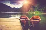 View of glacial mountain Lake Biogradsko, wooden pier and boats in forest. Biogradska Gora National Park. Montenegro. Filtered image:cross processed vintage effect.
