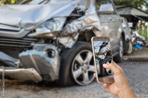 Hand of woman holding smartphone and take photo of car accident Poster