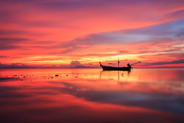 Silhouette traditional longtail boat and beautiful red sky and s