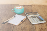 calculator, pen and cup of coffee on wood