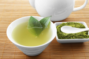 Fresh matcha tea on mat background