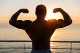 Silhouette of muscular showing biceps at sunnrise