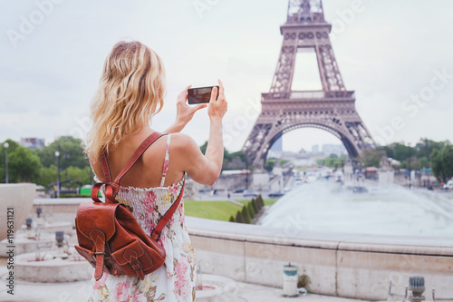 Poster tourist taking photo of Eiffel tower in Paris with compact camera or smartphone, travel in Europe