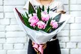 woman with bouquet of pink peonies in kraft paper