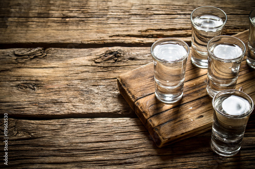 Plakat Glasses with vodka on the old Board.
