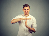 Young angry man showing time out hand gesture