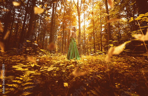 Frau mit grünem Abendkleid in herbstlichem Wald