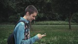 Young contemporary man walking in the park and texting on his phone using app on smartphone