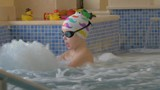 View of boy in playing with toy in the kids swimming pool. Small boy putted on swimming cap and goggles.