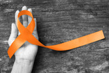 Orange ribbon for Leukemia, Kidney cancer, RDS multiple sclerosis awareness on human hand, aged background; Satin fabric color symbolic concept for raising public support on people living with disease