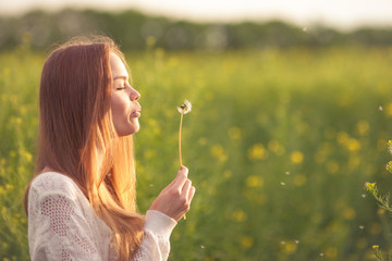 Young spring fashion woman blowing dandelion in spring garden. Springtime. Trendy girl at sunset in spring landscape background. Allergic to pollen of flowers. Spring allergy.