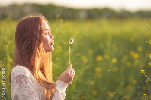 Young spring fashion woman blowing dandelion in spring garden. Springtime. Trendy girl at sunset in spring landscape background. Allergic to pollen of flowers. Spring allergy. - 119741545