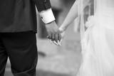 Coppia di neo sposi si tiene per mano appena dopo il matrimonio