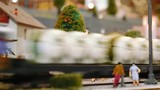 Model tram arrives then two trains pass by on a diorama