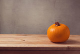Pumpkin on wooden table over rustic background