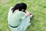芝生の上で落ち込む女性