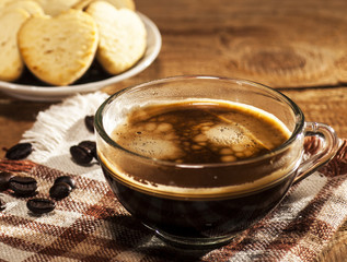Glass cup with coffee and cookies in a heart shape