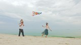Carefree and happy parents playing with daughter and a kite. On the beach