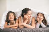 Mother having fun with children in the bed