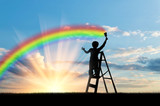 Child paints a rainbow in the sky - 119814145