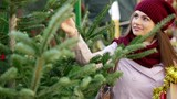 Happy woman   buying Christmas tree in market