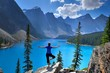 Woman in yoga pose at alpine lake and mountains. Moraine Lake in Rocky Mountains. Banff National Park, Alberta, Canada.
