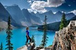 Woman looking at view of lake and mountains. Moraine Lake in Rocky Mountains. Banff National Park, Alberta, Canada.