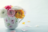Colorful ranunculus flowers in a decorative cup