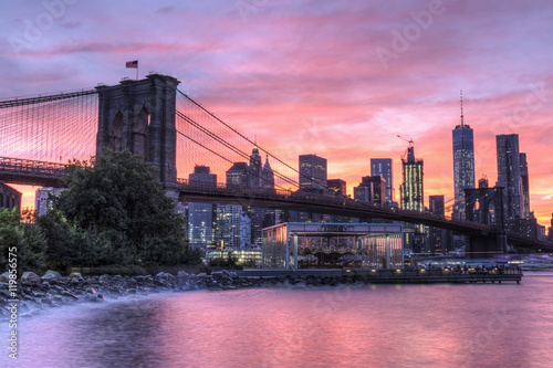 A colorful twilight view of the Brooklyn Bridge, Jane's Carousel and the Manhattan skyline see from Empire Fulton Ferry Park in Brooklyn Poster