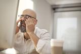 Fototapety Senior businessman rubbing his tired eyes